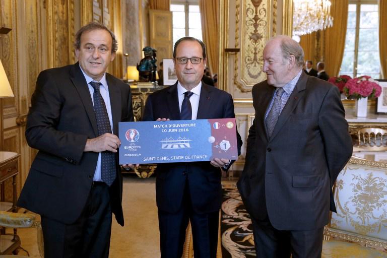 UEFA Präsident Michel Platini (L) und der Vorsitzender der Organisation der UEFA EURO 2016 Jacques Lambert (R) überreichen ein Euro 2016 ticket an den französischen Präsidenten Francois Hollande im Elysee Palast in Paris am 10.Juni 2015, genau ein Jahr vor dem Start der Euro 2016. AFP PHOTO / POOL / YOAN VALAT