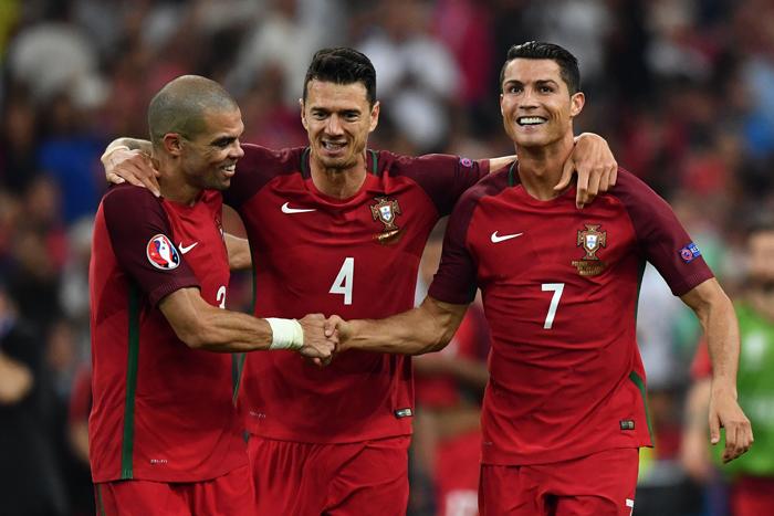 Portugals Pepe, Fonte und Cristiano Ronaldo feiern das 5:3 nach Elfmeterschießen gegen Polen und stehen somit im EM-Halbfinale. / AFP PHOTO / BERTRAND LANGLOIS